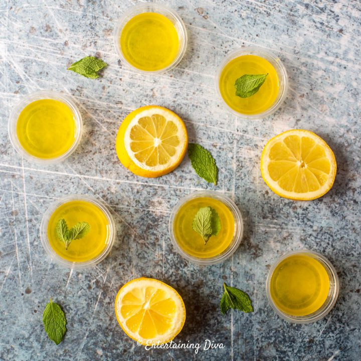 Lemon drop jello shots with slices of lemon and mint leaves