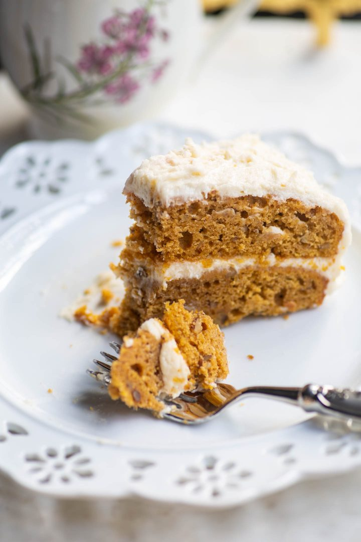Pumpkin spice layer cake with cream cheese icing on a plate with a bite out of it