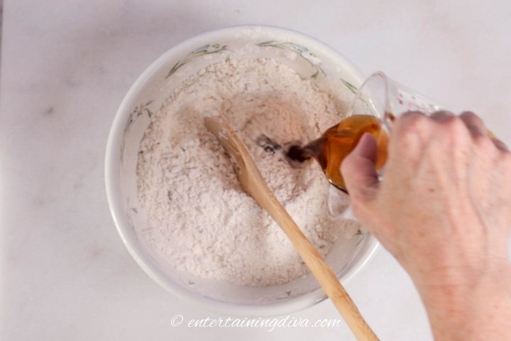 Maple syrup being added to the flour mixture in a bowl