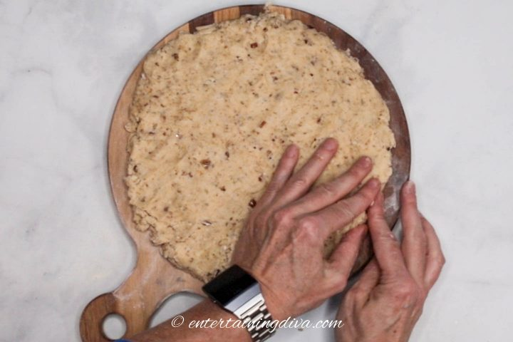 Scones dough being patted out to form a circle on a cutting board