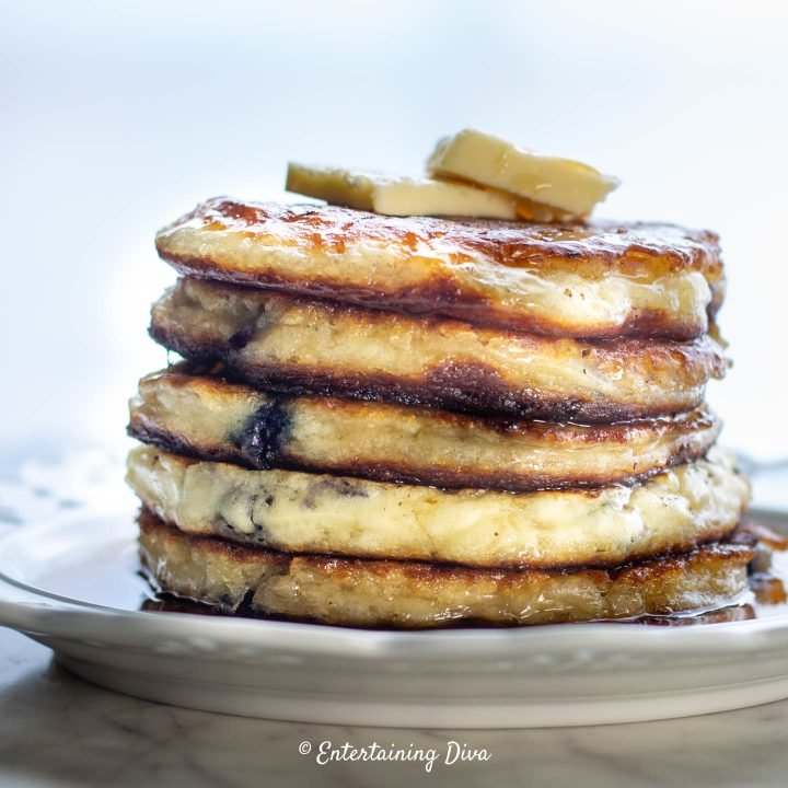 A stack of gluten-free buttermilk pancakes with butter and maple syrup
