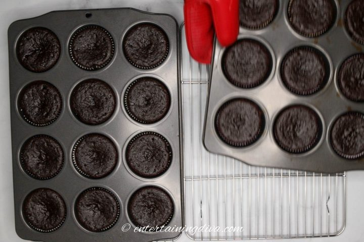 Muffin tins with chocolate cupcakes cooling on wire racks