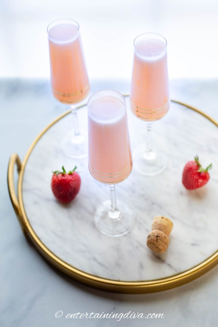 strawberry mimosas in champagne flutes on a marble tray