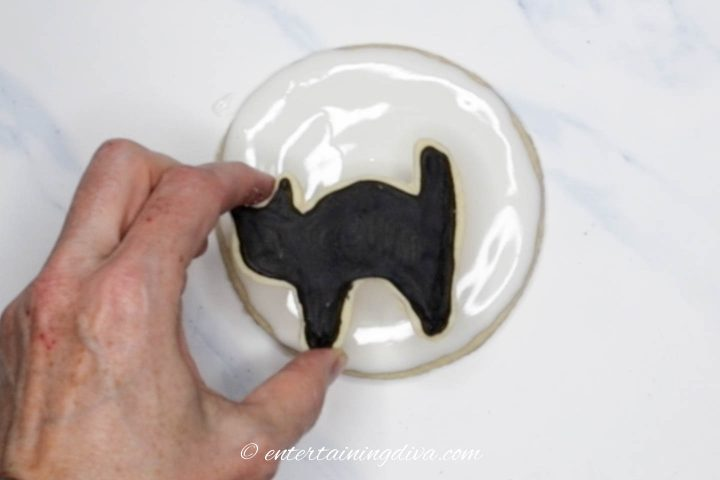 Black cat cookie being placed on the moon cookie