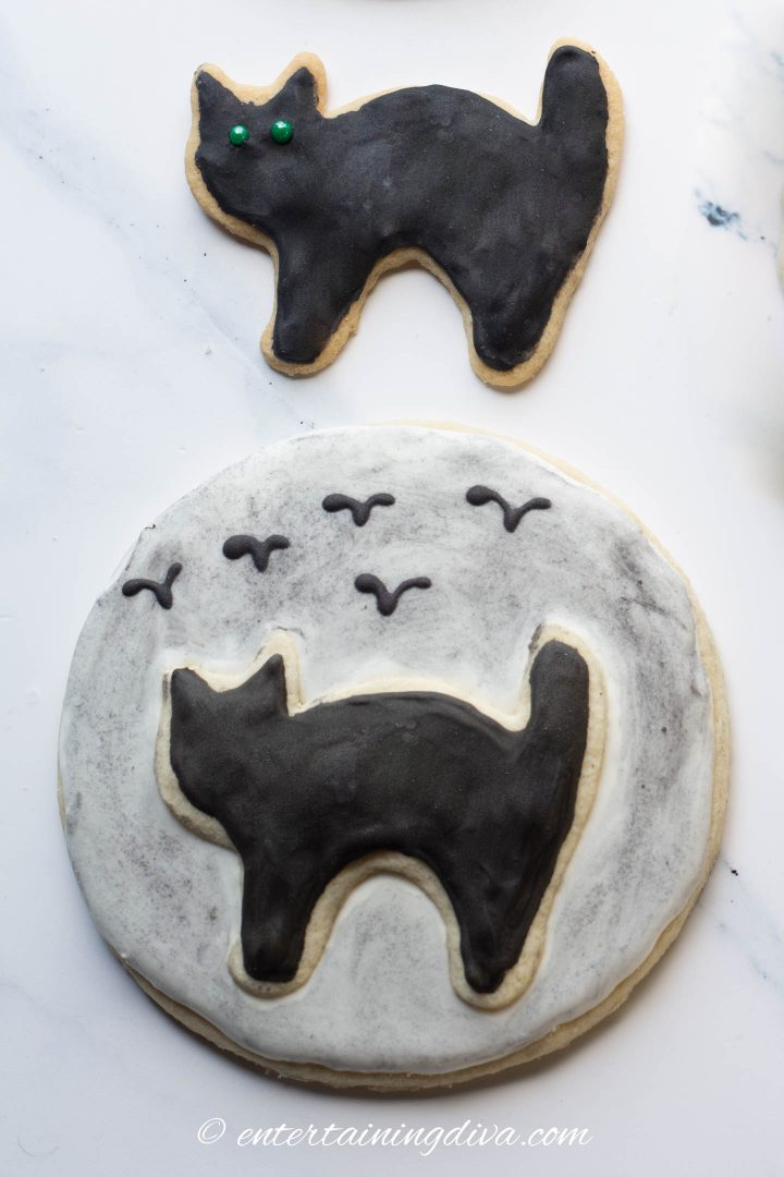 black sugar cookie and a black cat silhouette in front of the moon cookie