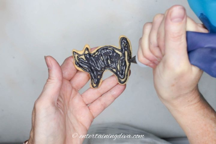 Black icing being flooded onto cat cookie