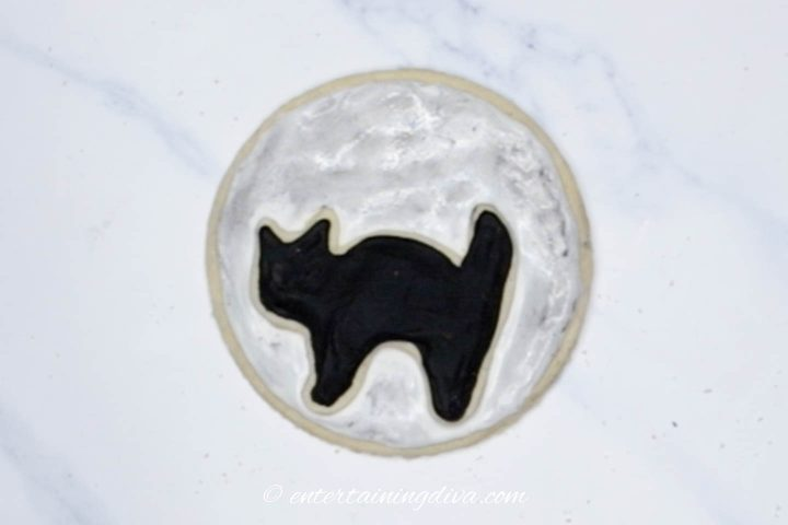 The silhouette cat cookie in front of a midnight moon cookie