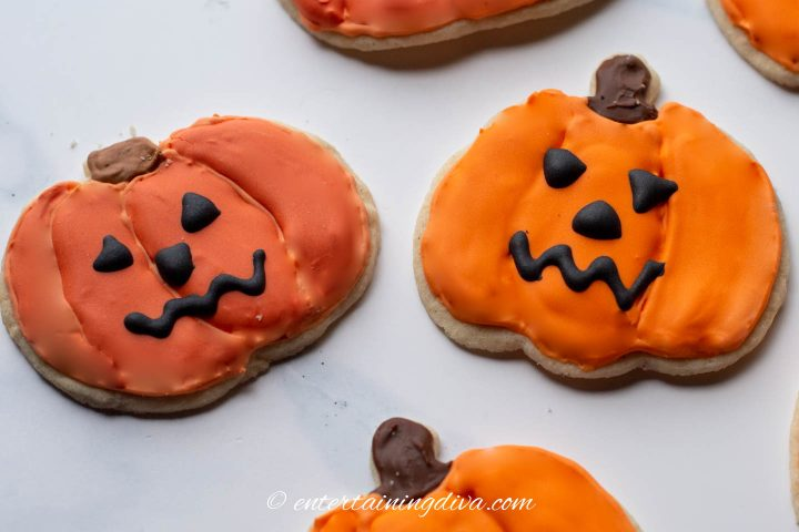Decorated pumpkin cookies made with homemade orange food coloring and AmeriColor Orange food coloring