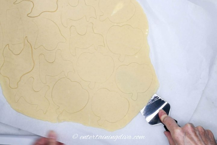 Pumpkin cut-outs being separated from parchment paper by a spatula