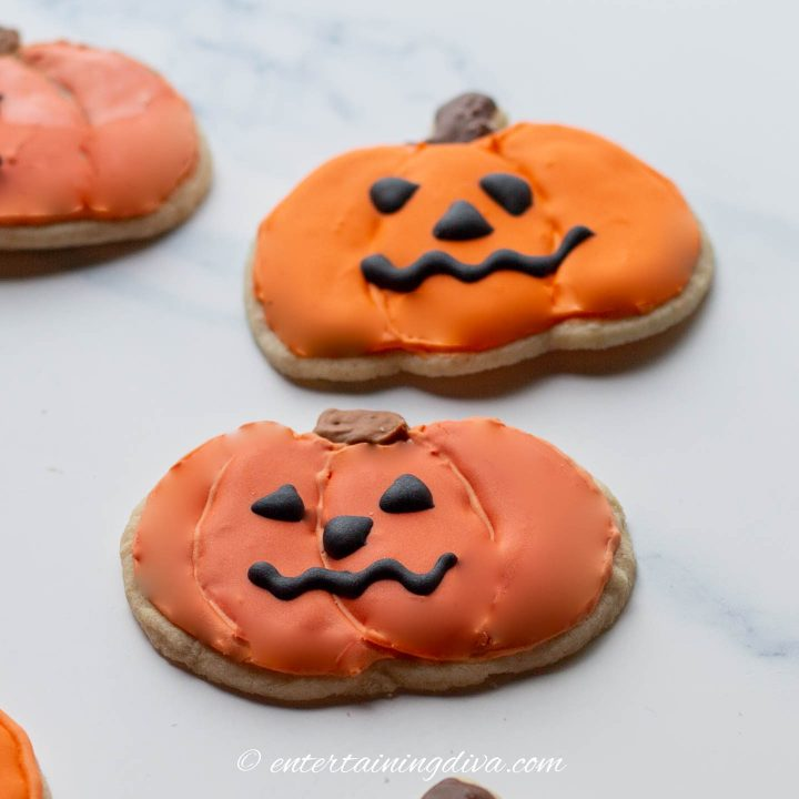 Halloween pumpkin cookies decorated with black royal icing faces