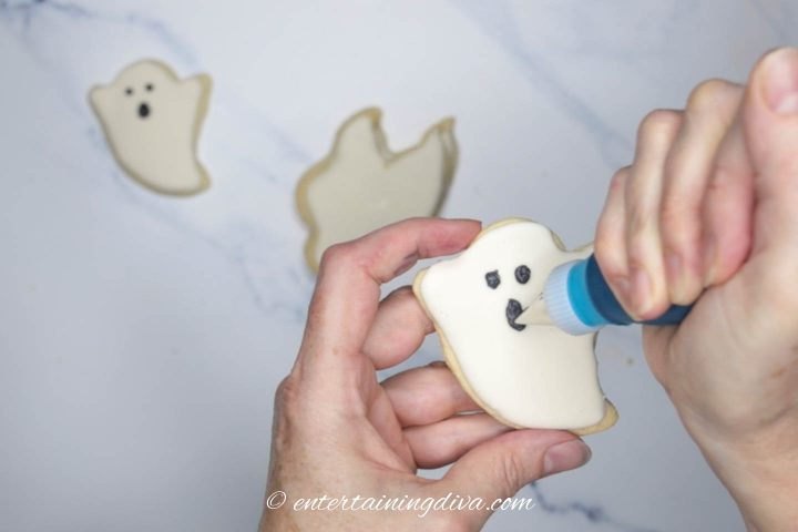 Black royal icing face being piped on a ghost cookie