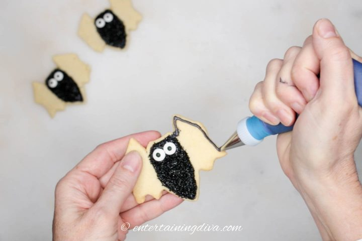 Wings of the bat cookie being outlined with black royal icing