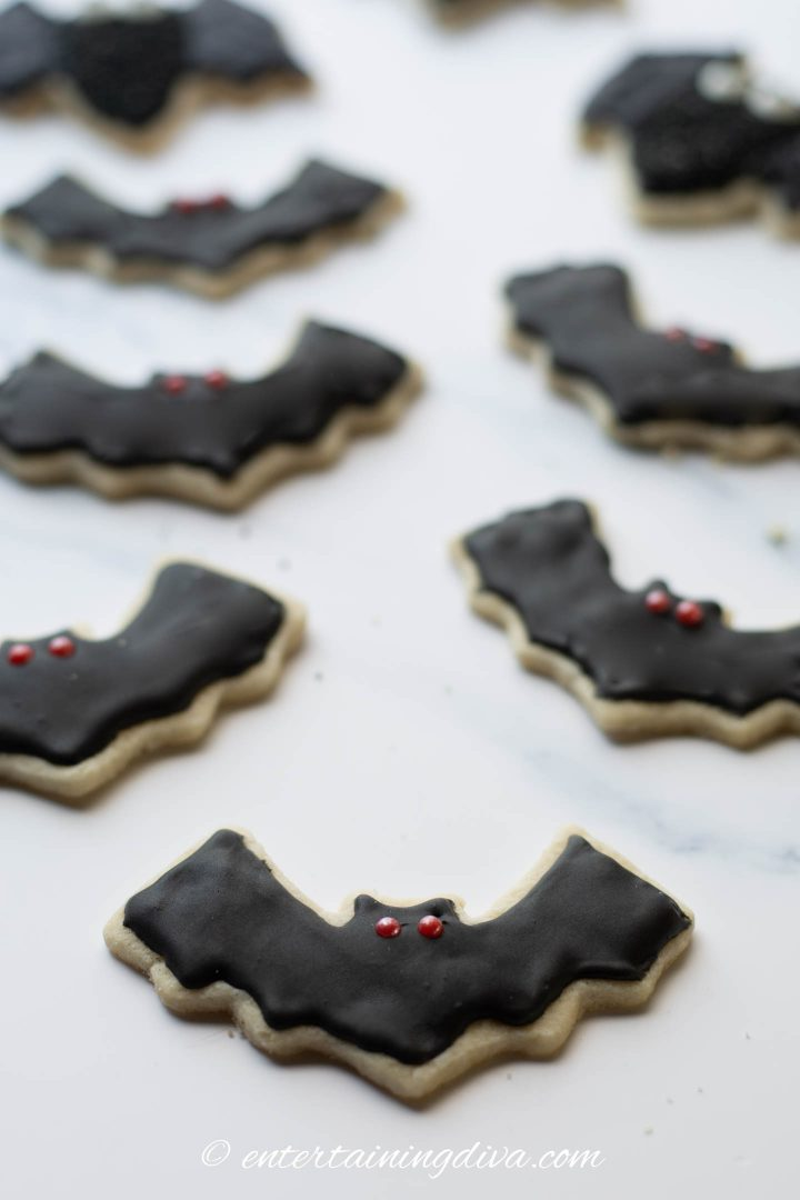 Halloween bat sugar cookies decorated with black royal icing and red sugar pearl eyes