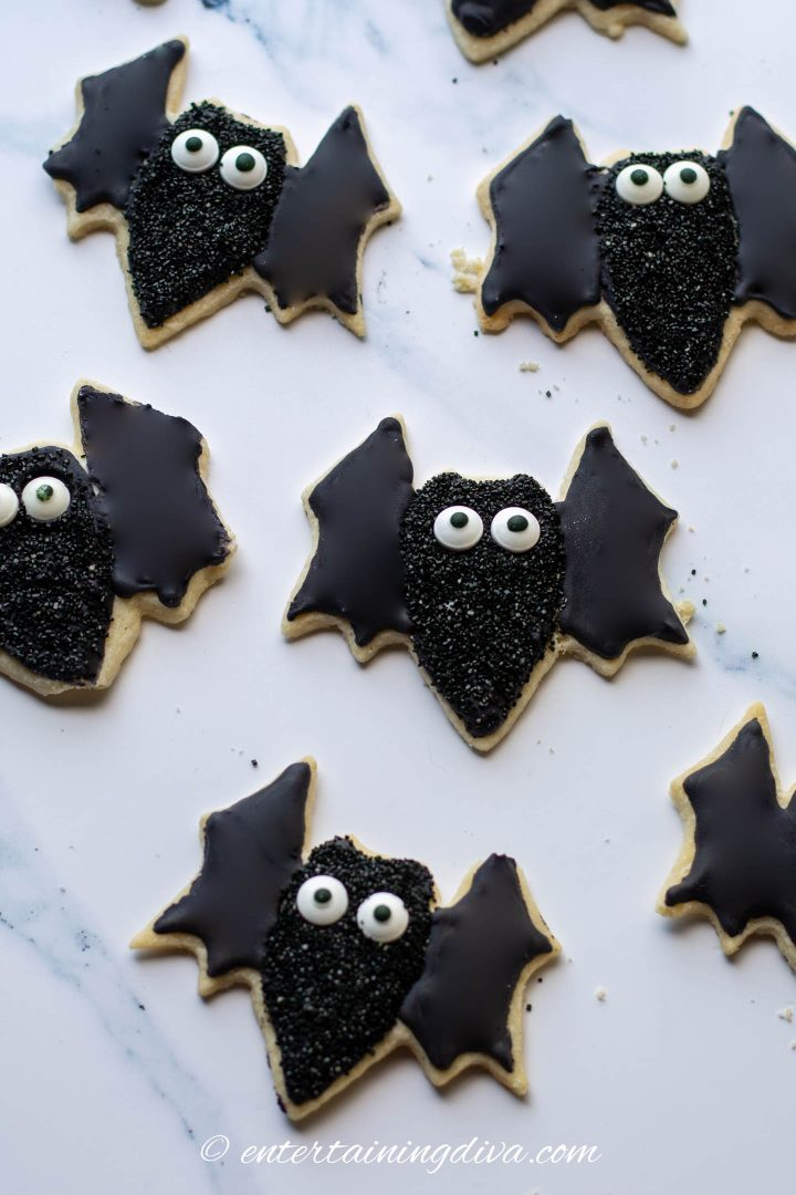 Larger Halloween bat sugar cookies with black royal icing, black sprinkles and candy eyes.