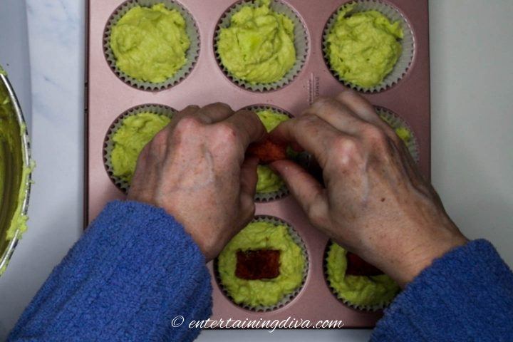 Hearts being pushed into the green cupcake batter