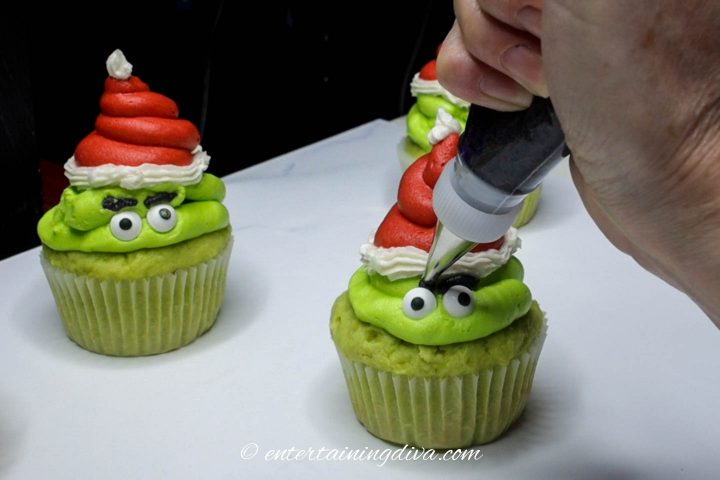 Green Grinch cupcakes with eyes and eyebrows being piped on with black icing