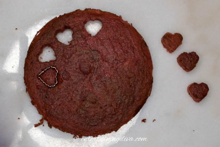 small hearts being cut out of a red velvet cake layer