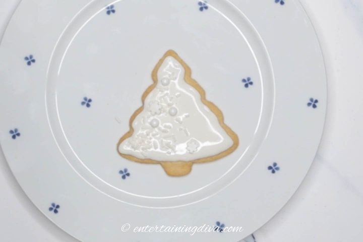 Christmas tree sugar cookies with white icing and white sprinkles