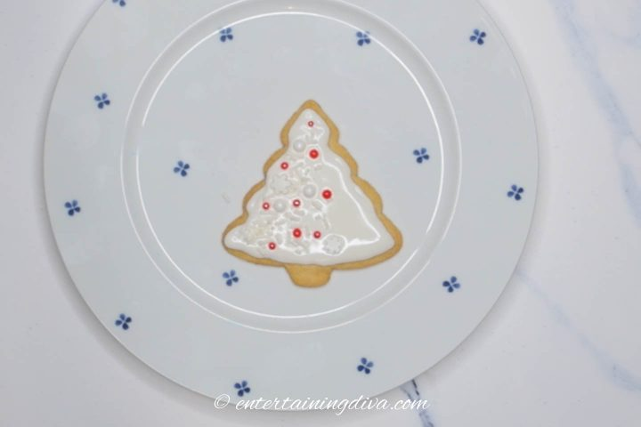 Christmas tree sugar cookies decorated with white icing and red and white sprinkles