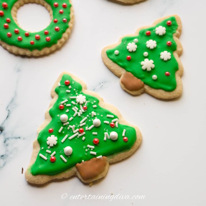 Christmas tree sugar cookies decorated with green icing and white and red sprinkles
