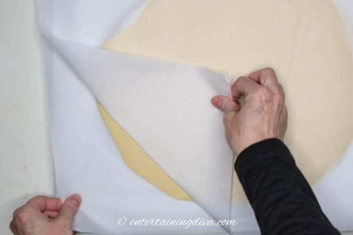 Parchment paper being peeled off the chilled cookie dough