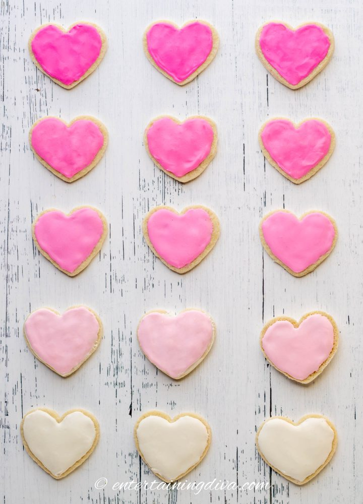 heart cookies frosted with different shades of pink royal icing