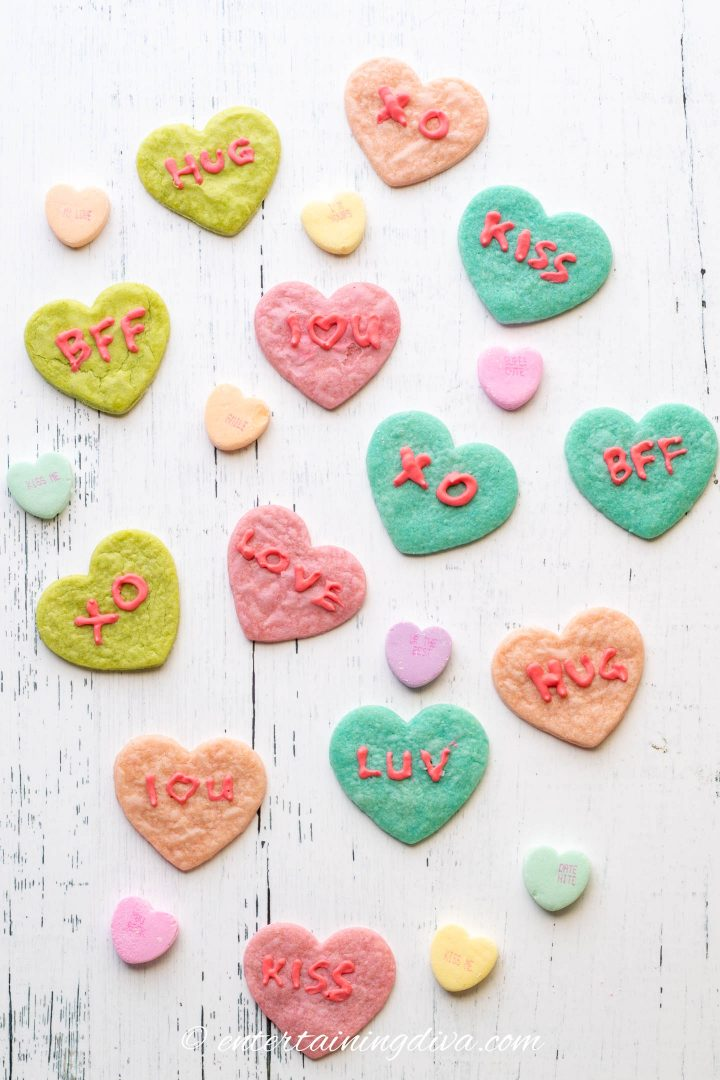 Heart cookies in different colors of cookie dough with conversation heart sayings in red royal icing