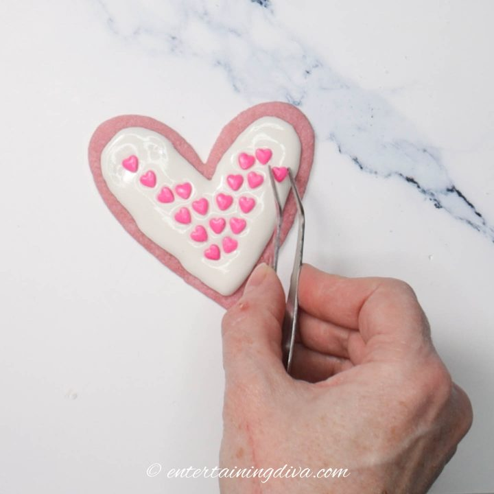 Heart cookie decorated with white royal icing and pink heart sprinkles