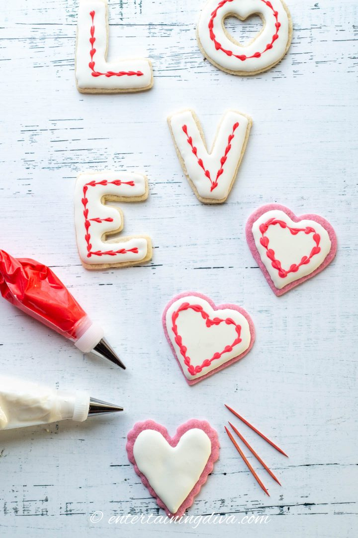 Heart cookies and LOVE cookies decorated with white royal icing and a red joined heart outline
