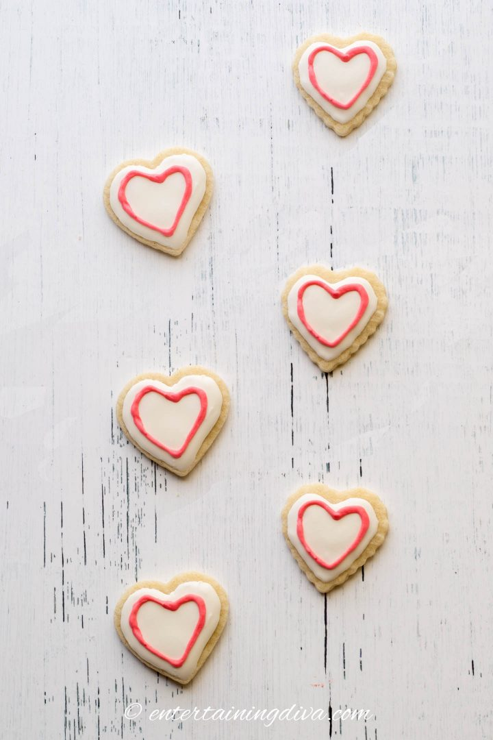 Heart cookies decorated with white royal icing and red outline