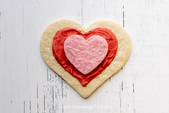 A smaller pink heart cookie stuck to a larger white heart cookie with red royal icing drawn in a heart design