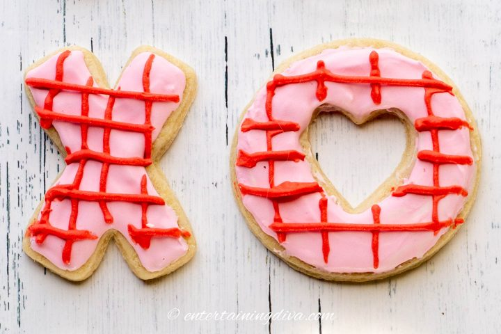 Valentine cookies in an X O shaped decorated with pink royal icing and red criss-cross pattern