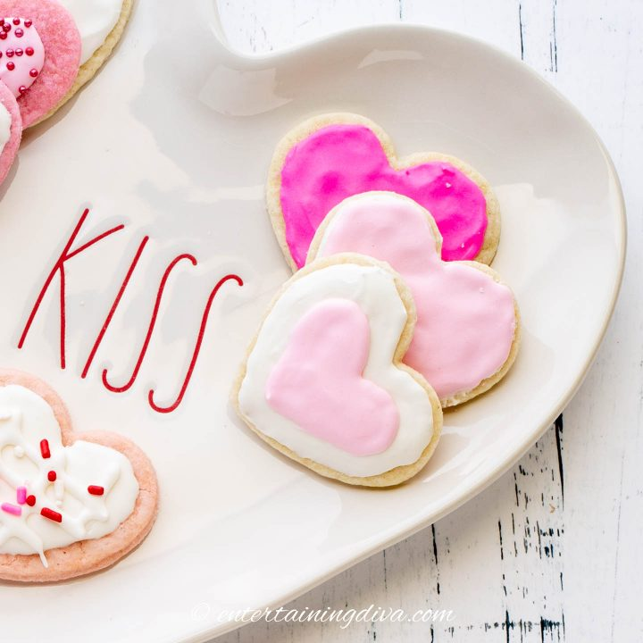 Heart cookies with pink and white royal icing on a heart-shaped plate