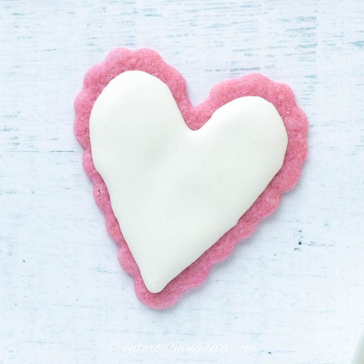 Heart cookie made from a pink sugar cookie with white royal icing