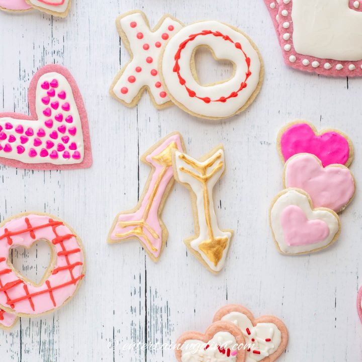 Valentine cookies decorated with white and pink royal icing and gold edible paint