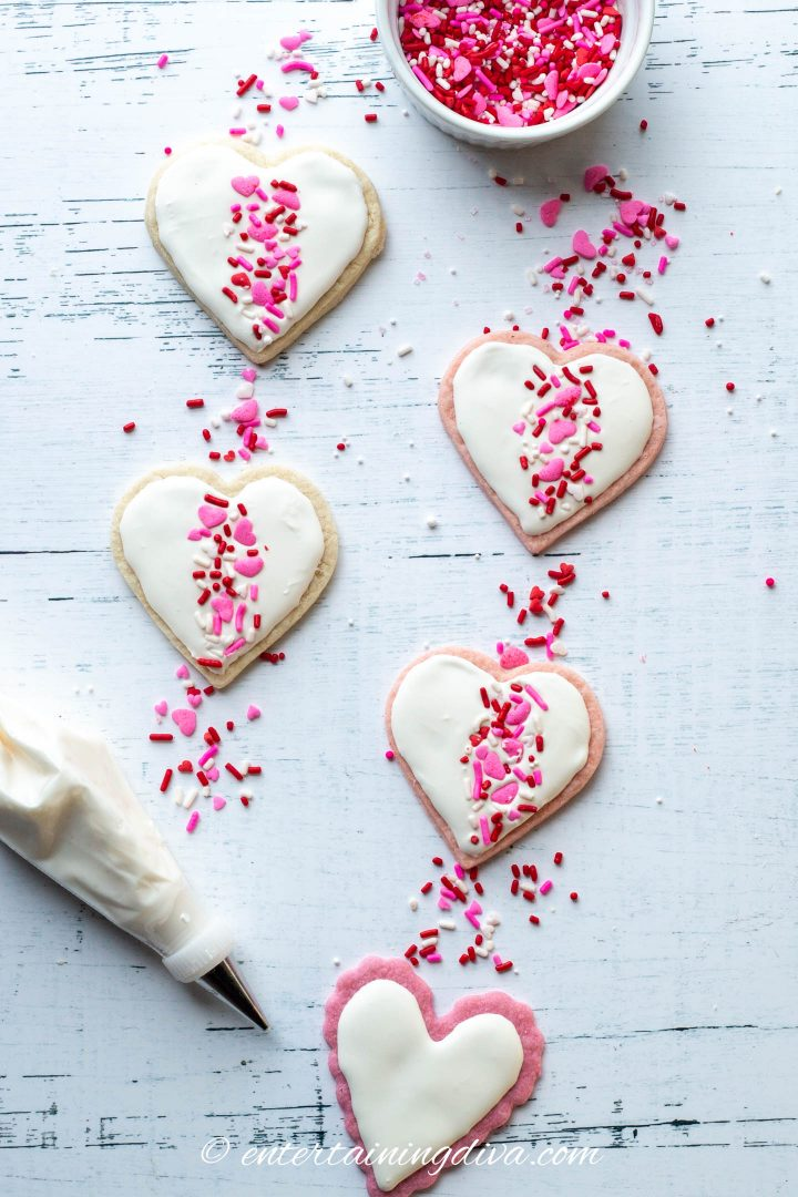 Heart cookies decorated with white icing and pink, white and red sprinkles in a band down the middle