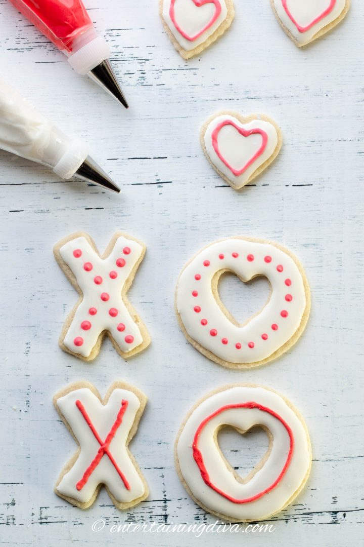 Cookies in an X and O shape decorated with white royal icing and red dots