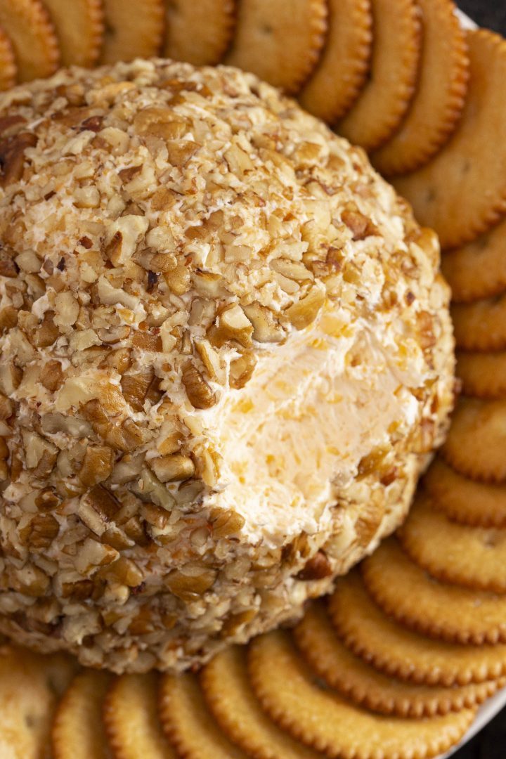 Three cheese ball coated with nuts on a plate with crackers