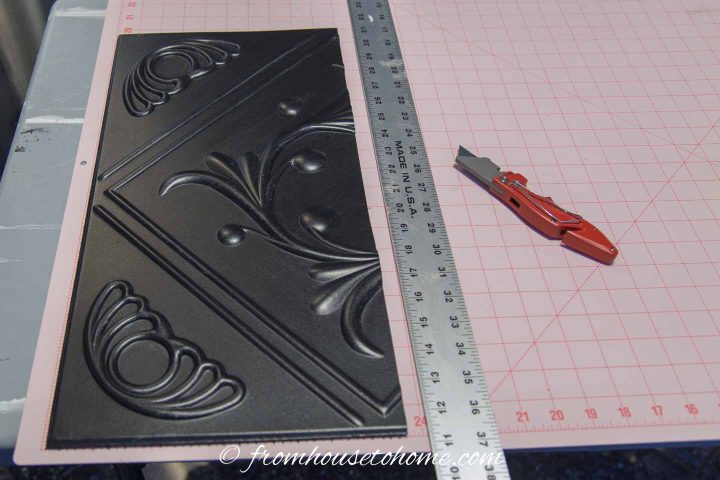 Styrofoam faux tin ceiling tile cut with utility knife
