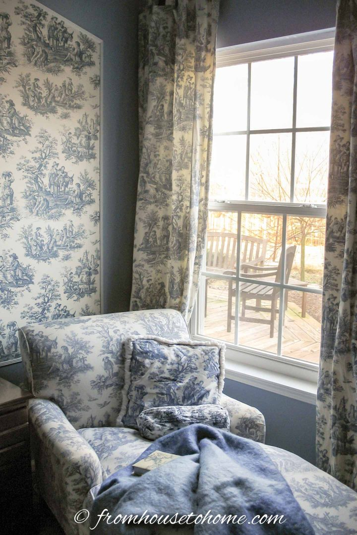 Blue and white toile wallpaper inside panel moldings on a light blue wall
