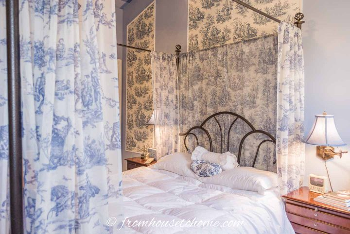 Blue and white toile sheers hung from a canopy bed