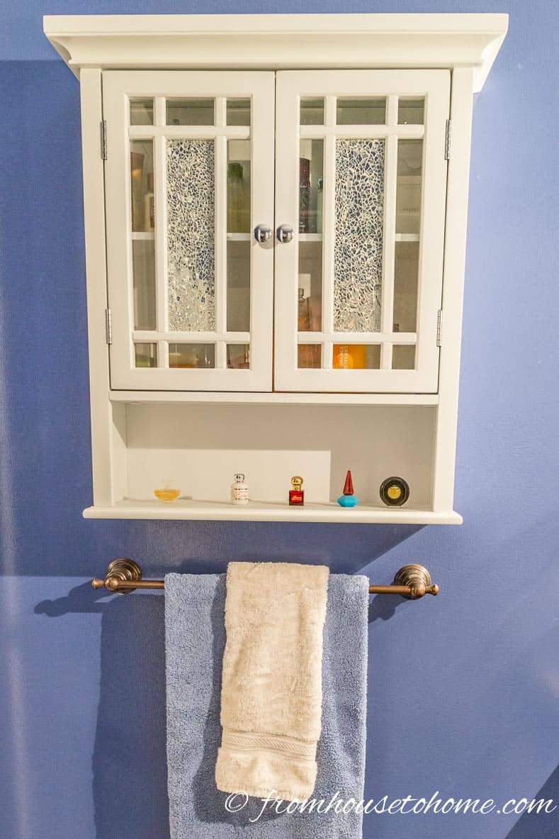 This very narrow storage cabinet stores shampoo, soaps, bubble bath and other bathroom necessities | How to Renovate a Small Bathroom on a Budget