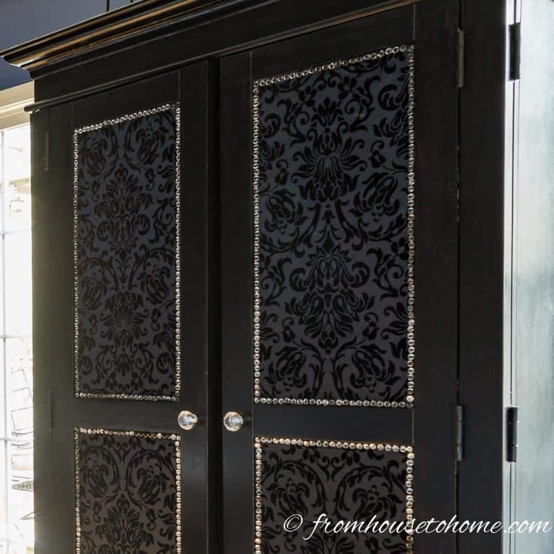 Crystal nail head trim on a modern glam armoire