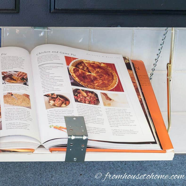 The DIY under cabinet cookbook shelf holding a large cookbook