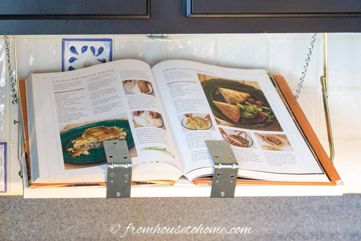 The finished DIY under cabinet cookbook shelf with a large cookbook on it