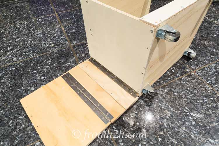 Attach the last hinge on the edge of the last board to the back of the drawer unit