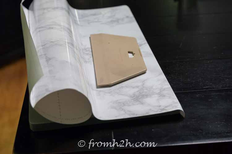 Use the smoother to stick the contact paper to the board | DIY Faux Marble Table