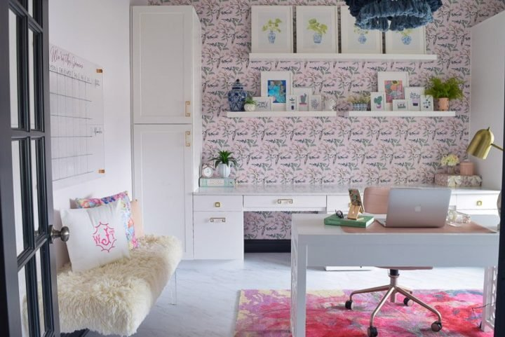 Glam home office with pink and blue wallpaper, white fur bench and a blue tassel chandelier