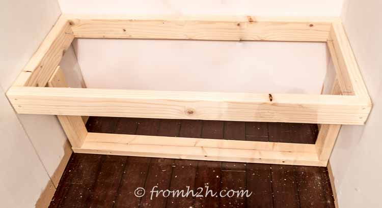 Screw the top bench frame to the wall and the sides of the shelf | DIY Bonus Room Bookshelves And Window Bench