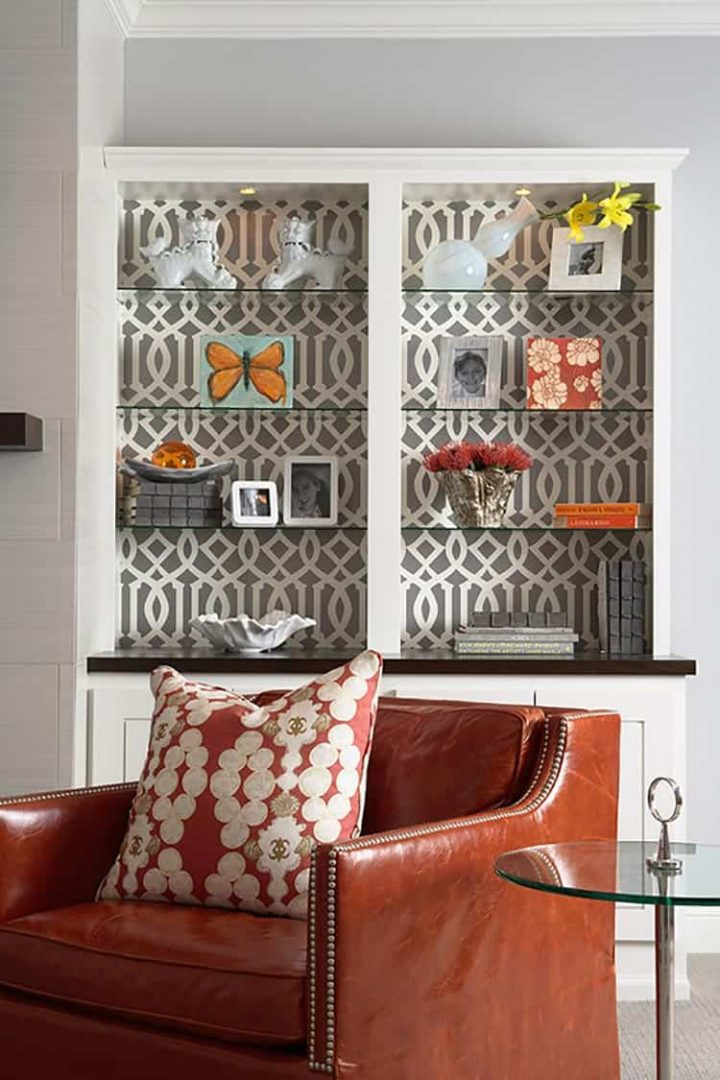 Bookshelf with wallpaper covering the back and glass shelves, by Martha O'Hara Interiors